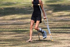 Accident tourist girl are walking by crutches in the garden. Royalty Free Stock Photography