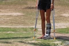 Accident tourist girl are walking by crutches in the garden. Stock Photography