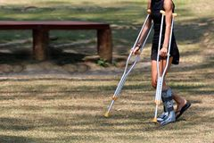 Accident tourist girl are walking by crutches in the garden. Royalty Free Stock Images