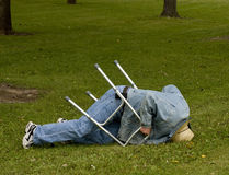 Accident with a walker. Elderly man falls down with a walker on a lawn Stock Image