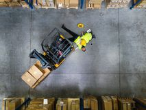 Warehouse workers after an accident in a warehouse. An accident in a warehouse. Woman performing cardiopulmonary resuscitation. Aerial view stock images
