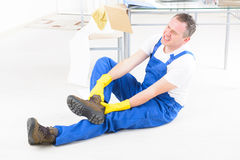 Accident at work. Man worker with ankle injury, concept of accident at work royalty free stock photo