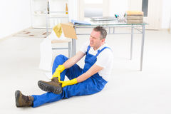 Accident at work. Man worker with ankle injury, concept of accident at work Royalty Free Stock Photos