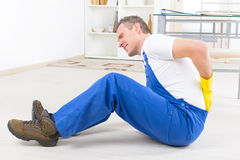 Accident at work. Man worker with back injury, concept of accident at work Royalty Free Stock Photos