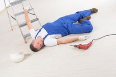 Accident at work. Man worker laying on a floor, concept of accident at work Royalty Free Stock Images