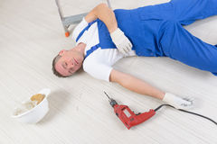 Accident at work. Man worker laying on a floor, concept of accident at work Royalty Free Stock Photo