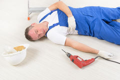 Accident at work. Man worker laying on a floor, concept of accident at work Stock Image
