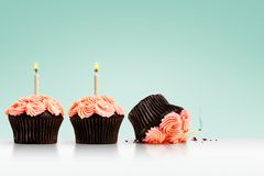 Smashed cupcake in row of cupcakes with candles on green. Accidentally dropped and smashed cupcake in row of cupcakes with lit candles flames and smoke on green Stock Image