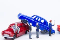 Accidente minúsculo miniatura del choque de coche de los juguetes dañado Seguro en Imagen de archivo