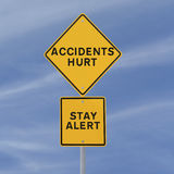 Accidents Hurt!. Road sign with a safety reminder against a blue sky background Royalty Free Stock Images