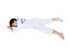 Accidents in sports. Asian child athletes taekwondo lying prone. Accidents in sports. Full body of asian child athletes taekwondo with white belt lying in  prone Royalty Free Stock Images