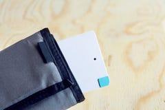 Accione el pequeño mini tamaño del banco en fondo de madera en el monedero, cartera Foto de archivo libre de regalías