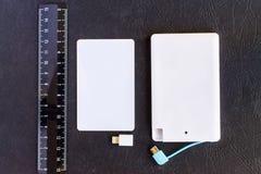 Accione el pequeño mini tamaño del banco en la tarjeta y las reglas de crédito en vagos negros Foto de archivo