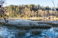 Accione la casa por el lago escarchado del invierno iluminado por el sol naciente Imagen de archivo