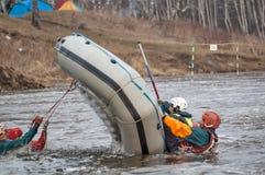 Acciones del trabajo de los atletas al volcar la balsa Foto de archivo libre de regalías