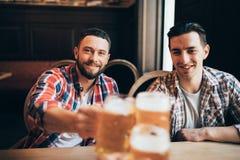 Acclamations de tasses de bières de boisson de prise de mains d'amis Image libre de droits