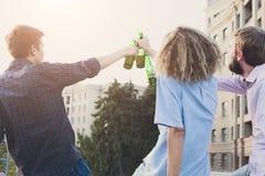 Acclamations heureuses d'amis avec de la bière extérieure Photo libre de droits