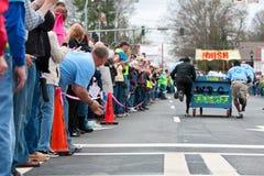 Acclamazione Team Pushing Bed Toward Finish degli spettatori della corsa della raccolta fondi Immagine Stock