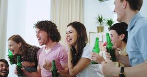 Acclamazioni bevente della birra del primo piano maturo attraente della gente con le bottiglie davanti alla TV mentre guardando u archivi video