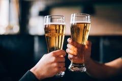 acclamazioni Un primo piano di due uomini in camice che tostano con la birra al contatore della barra Fotografia Stock