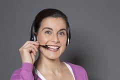 Accogliere favorevolmente operatore femminile 30s che risponde al telefono con le cuffie Fotografia Stock
