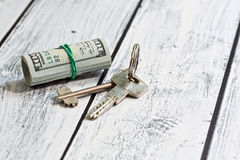 Accommodation payment concept. Stack of US currency paper - dollars - and a pair of door lock keys. Loan contribution or rental payment concept. Close-up capture Royalty Free Stock Photos