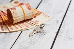 Accommodation or rental payment concept. Stack of russian currency papers - rubles - and a door lock key - on the wooden rough table. Rent estate payment or Royalty Free Stock Image