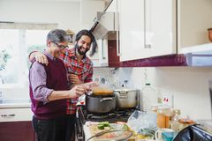 Accompanying Dad While he Cooks. Mid adult men is looking over his father`s shoulder as he prepares a curry at home stock photo