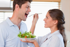 Accomplice couple tasting a salad Royalty Free Stock Photos