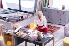 Accomplished elderly businesswoman looking at phone while working on drawing. Successful manager. Accomplished elderly attractive grey-haired businesswoman in stock image
