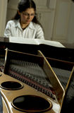 Accomplished Pianist at the Piano. View of an accomplished, prize-winning female pianist at the keyboard of an open grand piano with the internal structure and stock images