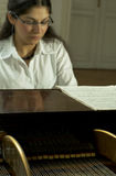 Accomplished Pianist at the Piano-2. An accomplished, internationally recognized and prize-winning female pianist sits at a grand piano with sheet music and some royalty free stock images