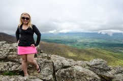 Accomplished smiling woman hiker poses at the summit of LIttle Stony Man, a hike in Shenandoah National Park in Virginia on a. Foggy day royalty free stock images