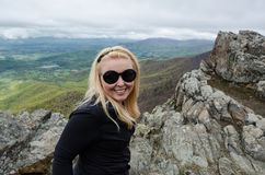 Accomplished smiling woman hiker poses at the summit of LIttle Stony Man, a hike in Shenandoah National Park in Virginia on a. Foggy day royalty free stock image