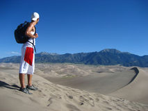 Accomplishment. A man gazes out over the Great Sand Dunes after having reached the top Stock Images