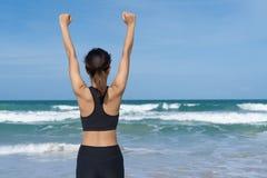 Accomplissements de sport et de vie et concept de succès Fille sportive de vue arrière soulevant des bras vers le beau soleil rou image stock