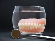 Accomplissez le dentier dans un verre image stock