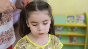 Acconciatura dei bambini Il parrucchiere fa l'acconciatura con capelli intrecciati stock footage