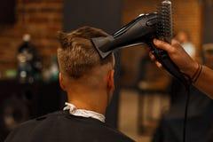 Acconciatura del ` s degli uomini Capelli che disegnano con un fon barbershop fotografie stock