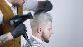 Acconciatura maschio in salone Essiccazione dei capelli dell'uomo nel negozio di barbiere Barbiere che disegna capelli con l'essi video d archivio
