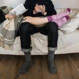 Accoppi in calzini di lana con una tazza di tè Fotografia Stock