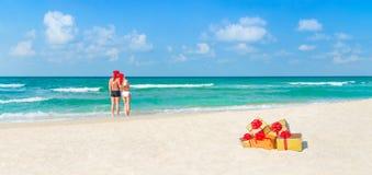 Accoppi in cappelli di Santa di Natale alla spiaggia con i regali di festa Fotografia Stock