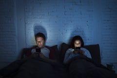 Accoppi a casa a letto tardi alla notte facendo uso del telefono cellulare nel problema di comunicazione di relazione Immagini Stock