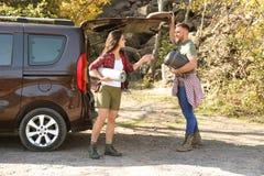 Accoppi dei campeggiatori con il sacco a pelo e la stuoia vicino all'automobile fotografia stock