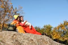 Accoppi dei campeggiatori in sacchi a pelo che si siedono sulla roccia immagini stock libere da diritti