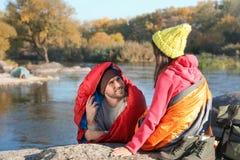 Accoppi dei campeggiatori in sacchi a pelo che si siedono sulla roccia vicino allo stagno fotografia stock libera da diritti