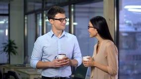 Accoppi dei compagni di squadra che chiacchierano durante la pausa caff?, atmosfera amichevole in ufficio fotografia stock