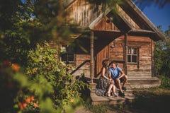 Accoppi gli uomini e le donne nel villaggio, vicino ad una casa di legno Stile country Estate rustica Fotografia Stock Libera da Diritti