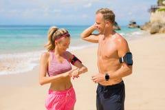 Accoppi i dispositivi della regolazione prima dell'allenamento sulla spiaggia Immagini Stock Libere da Diritti