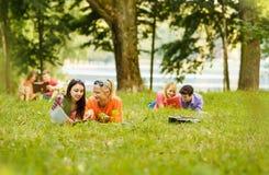 Accoppi i riusciti studenti con un manuale in un parco Fotografia Stock